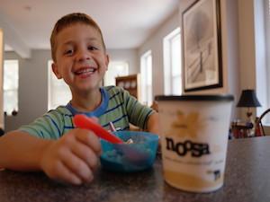 Child enjoying Noosa Yoghurt vanilla flavor.